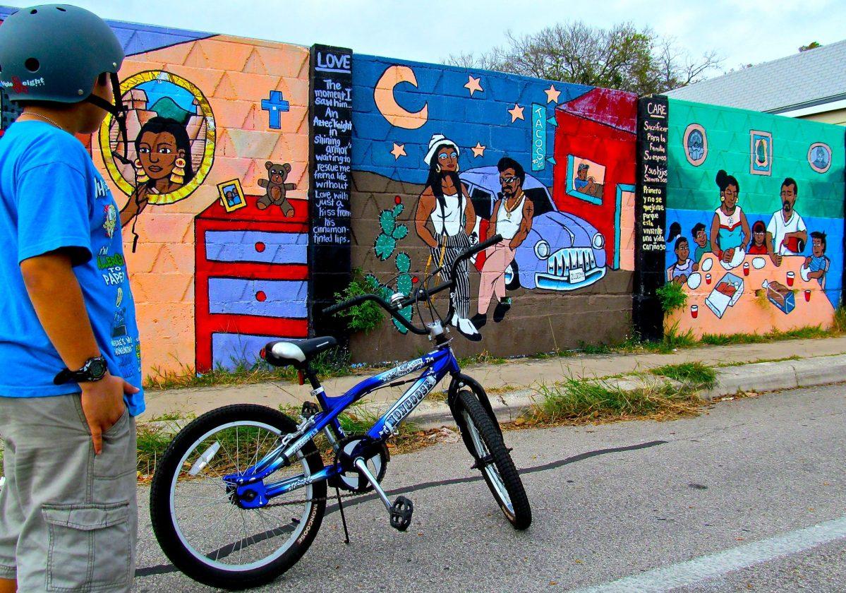 Young bike tour participant checks out a mural