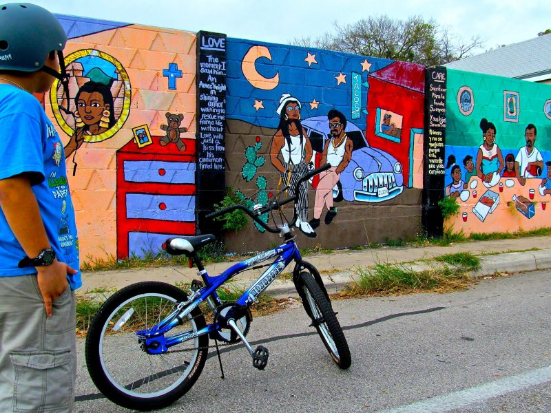 Young bike tour participant checks out a mural