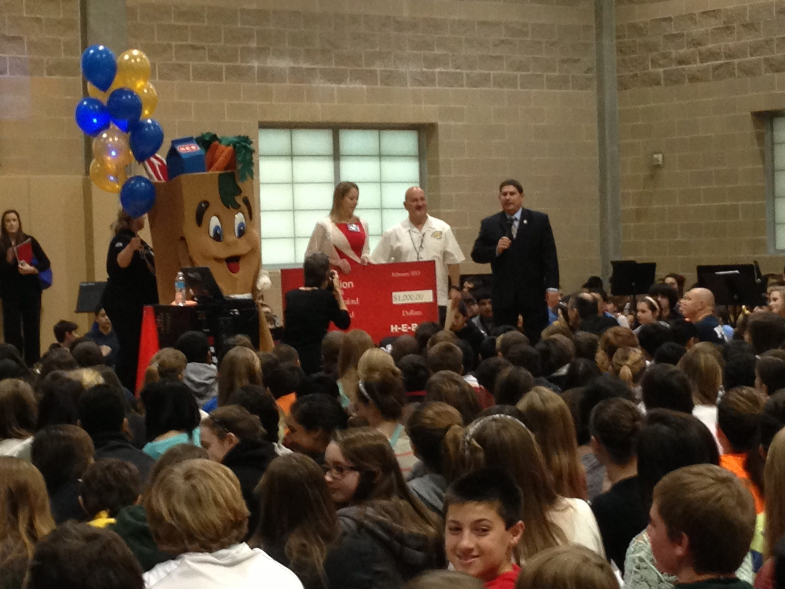 The HEB Buddy and Kimberly Harle present an H-E-B Excellence in Education check to award finalist Dr. Barry Lanford while Superintendent Brian Gottardy expresses his appreciation. A see of middle school students await another chance to cheer. Photo by Bekah McNeel.