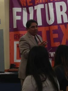 Principal Orlando Vera speaks to guests at Travis Early College High School