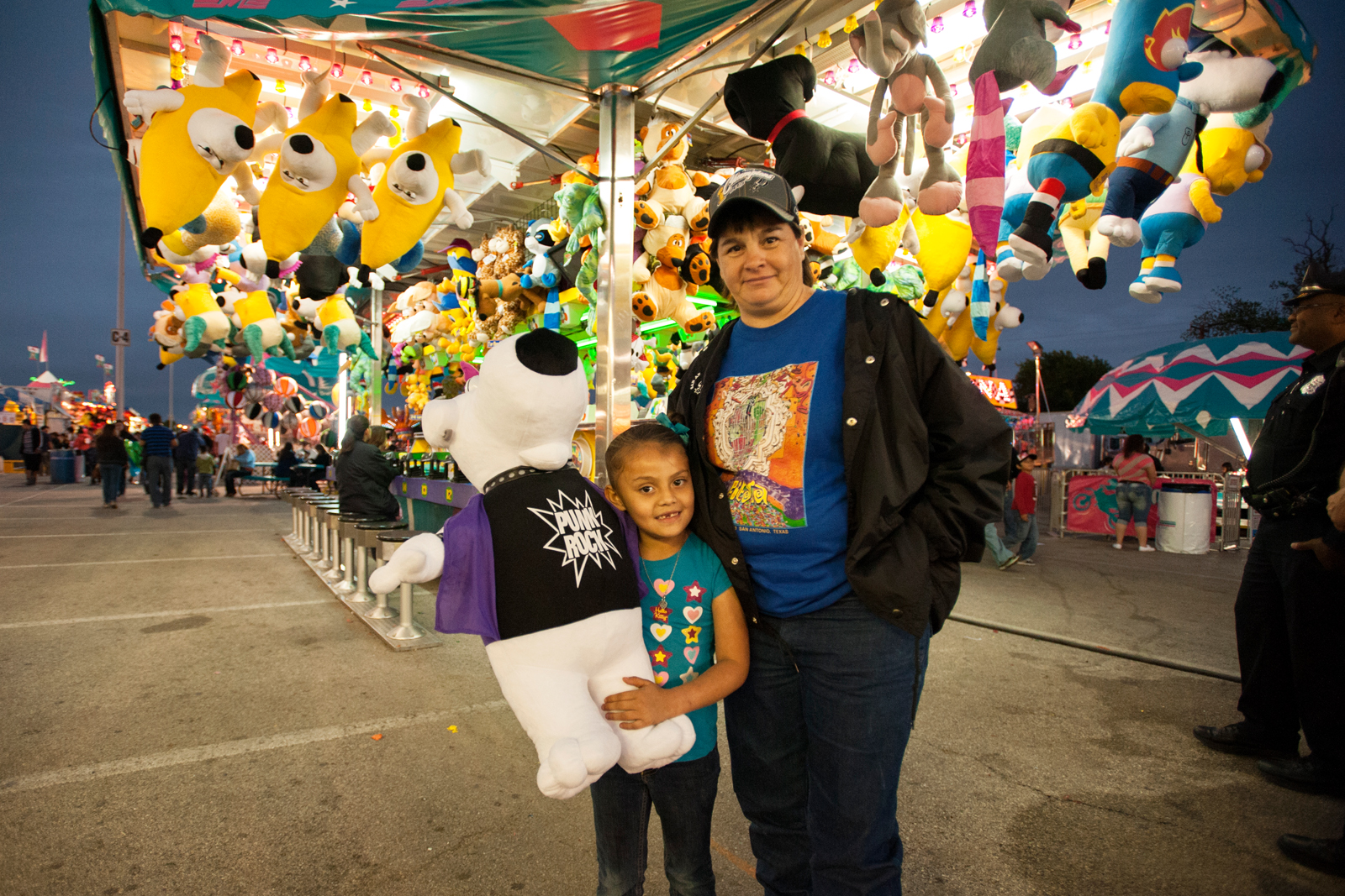 Pat Bravo poses with daughter Terry, age 6, after winning the water gun race at Fiesta Carnival. Photo by Corey Leamon.