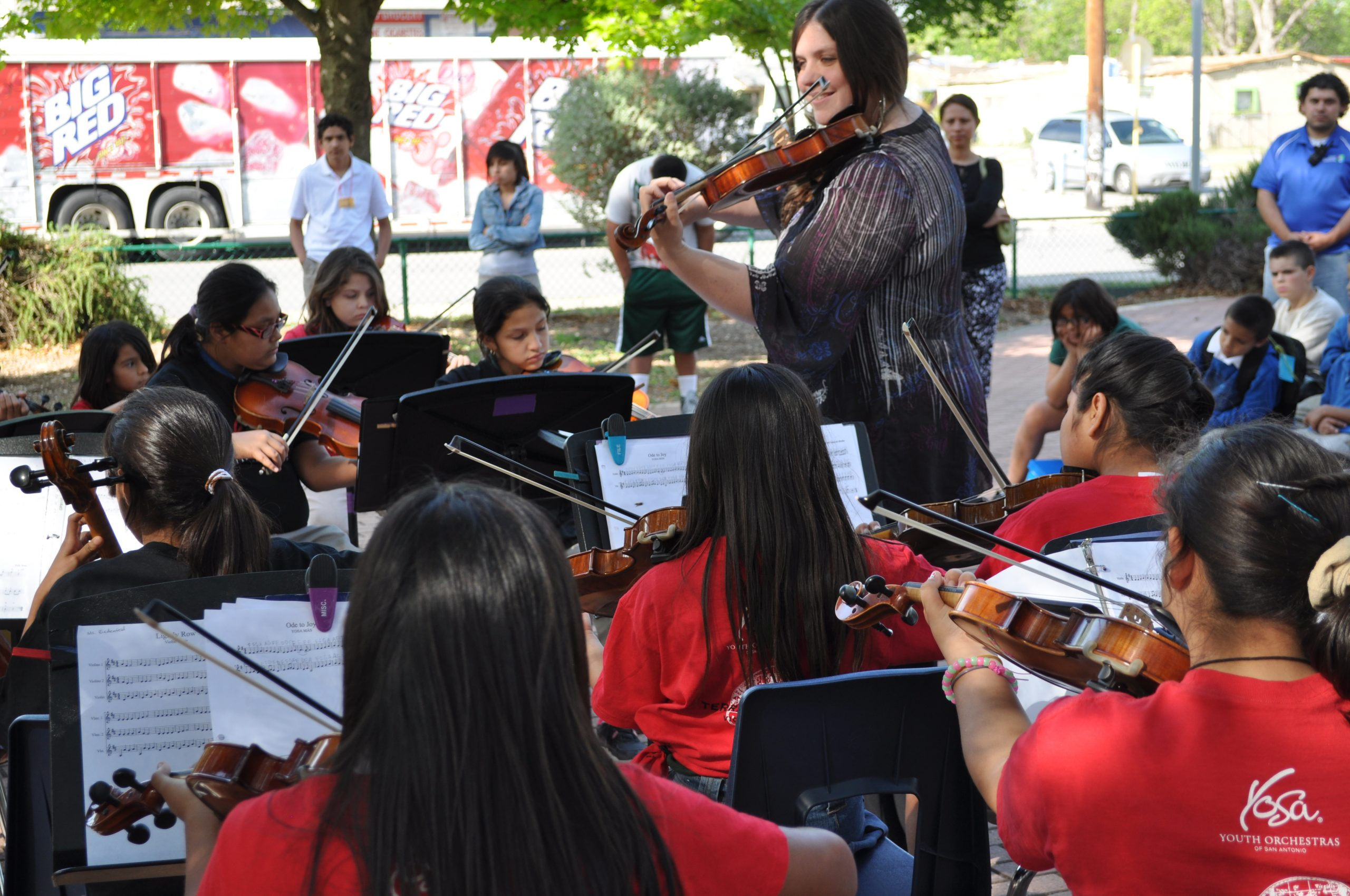 Maggie Raveneau, YOSA MÁS teaching artist, leads a miniature symphony of about 20 students. Photo by Iris Dimmick.