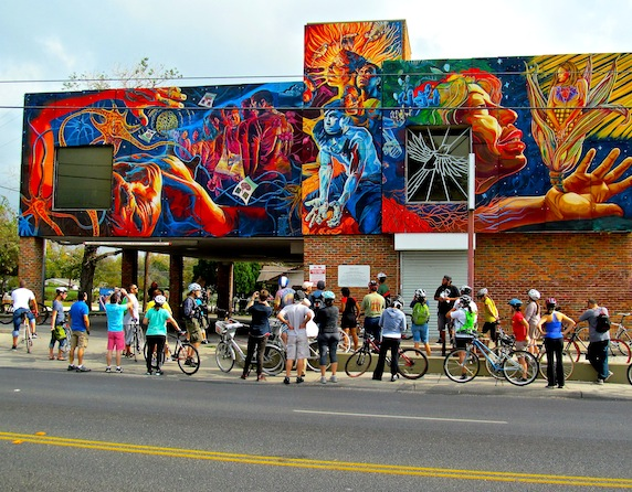 """Participants of the San Anto Cultural Arts Bike It! Mural Tour gaze at The Center for Health Care Services building. The mural, """"Brighter Days,"""" was painted in 2007 by Adriana Maria Garcia. Photo by Tom Trevino."""
