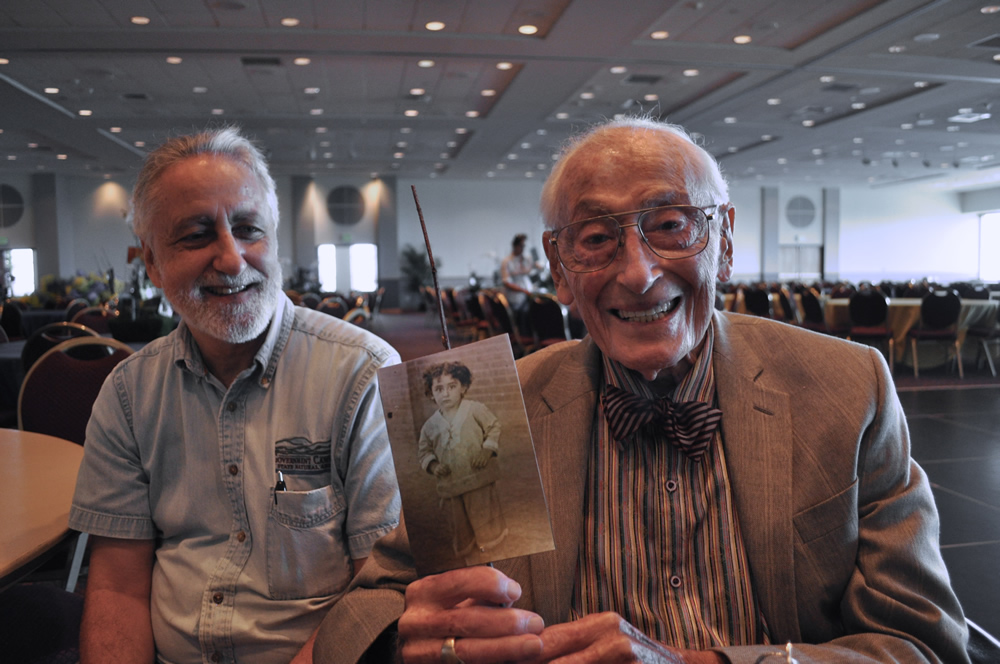 Lanny Sinkin sits with his father, Bill Sinkin, who officially turns 100 on Sunday, May 19, holds a photo of himself wearing the velvet suit he wore to school at age 6. Photo by Iris Dimmick.