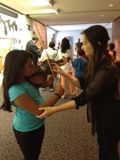 """Alysson Salazar, 10, from Heartman Elementary """"pets"""" a violin with a YOSA member, who guides her. Photo courtesy of YOSA."""