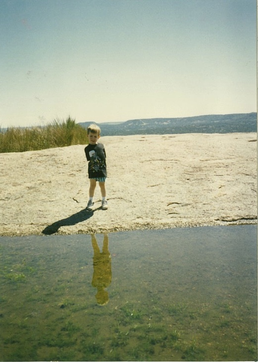 Vernal pools are depressions in the rock formed by centuries of weathering. These fragile ecosystems collect wind-blown soil and rainwater. Fertilized eggs of tiny invertebrates awaken from total disiccation with seasonal rains. Young Thomas Mathis views an emerging pool of moss while grass grows in a more developed pool at his back.