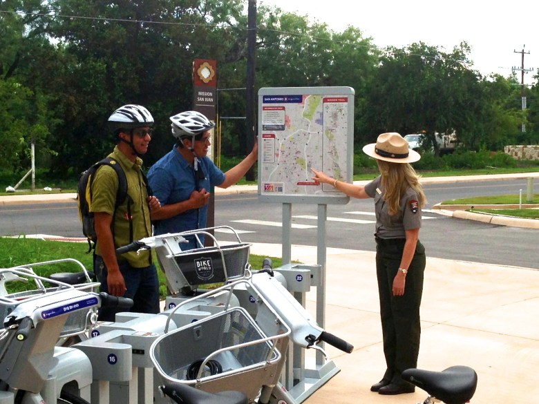 Two B-cyclist riders wearing their own helmets consult a Park Ranger along the Mission Reach of the San Antonio River. Photo by Julia Murphy/Office of Sustainability