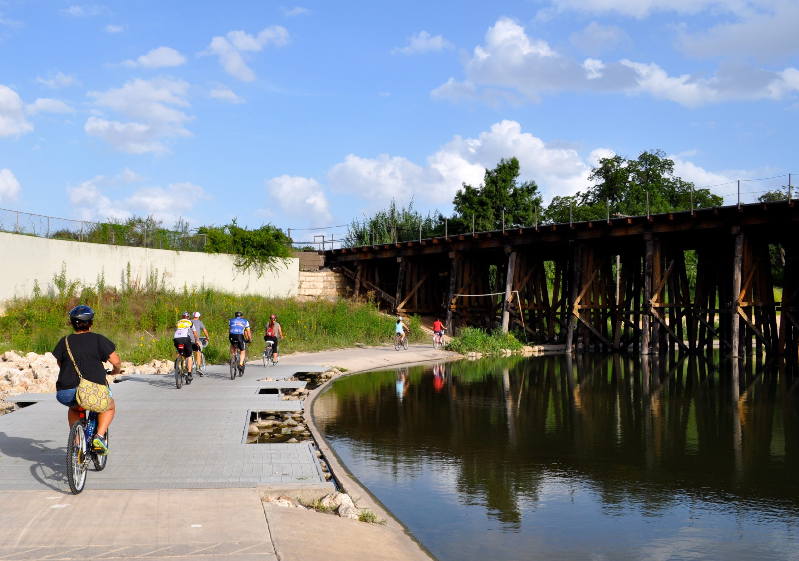 Riders cross under the train bridge on the Mission Reach during the Something Monday ride. Photo by Iris Dimmick.