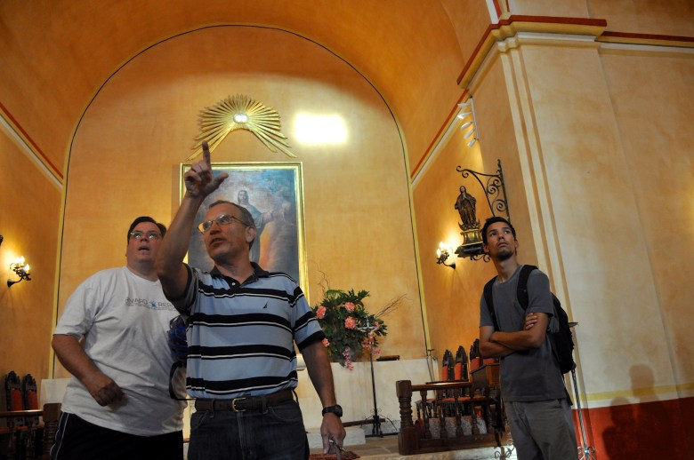 Fr. David Garcia points to the small openings that allow two beams of light to illuminate the Virgin Mary's face and altar floor at 6:30 p.m. every Aug. 15 for the Assumption of the Virgin Mary into Heaven. Photo by Iris Dimmick.