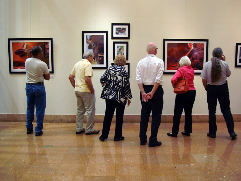 """Visitors enjoy the """"Point The Compass"""" exhibition, works by Josh Trudell, at the San Antonio Central Library Gallery during the opening Aug. 28. Courtesy photo."""