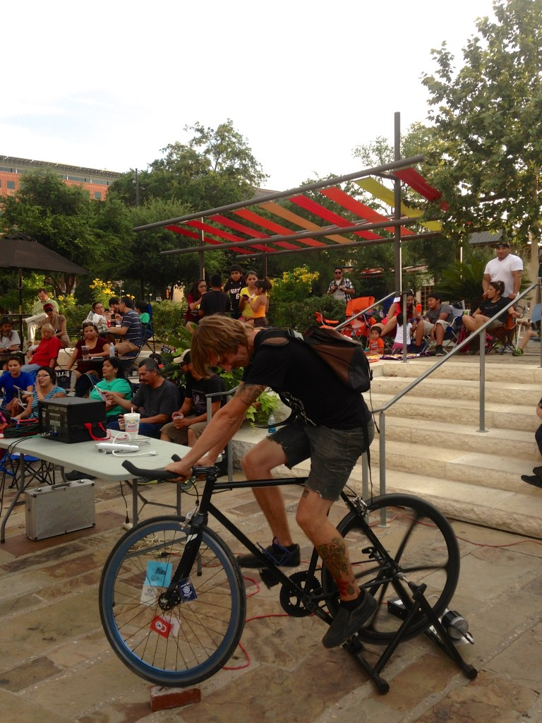A cyclist powers the SATX Pedal Power projector at dusk in Main Plaza on a recent Thursday night. Photo courtesy SATX Pedal Power.