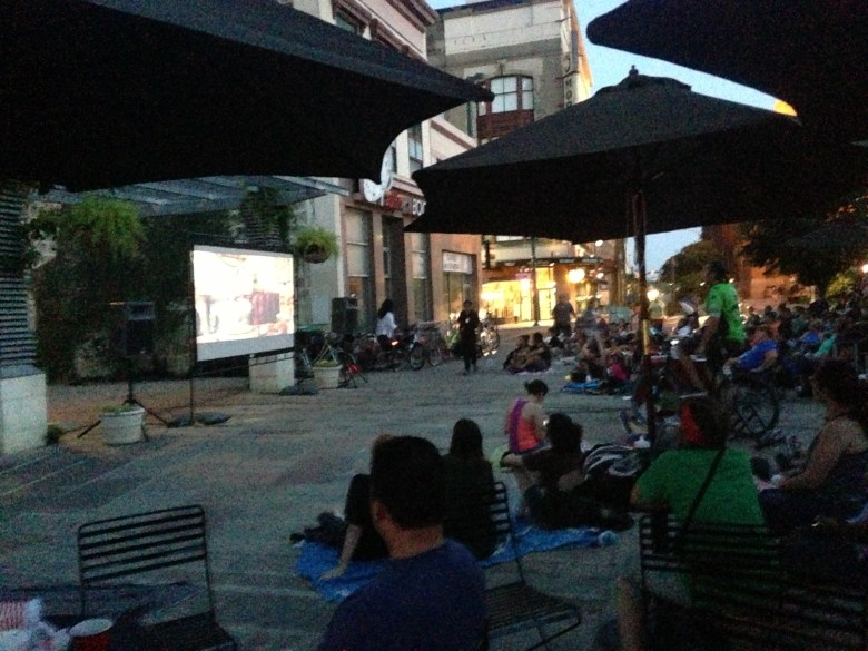 As the sun sets, locals and visitors watch classic films (typically from the 80s) in Main Plaza for Cycle-In Cinema.