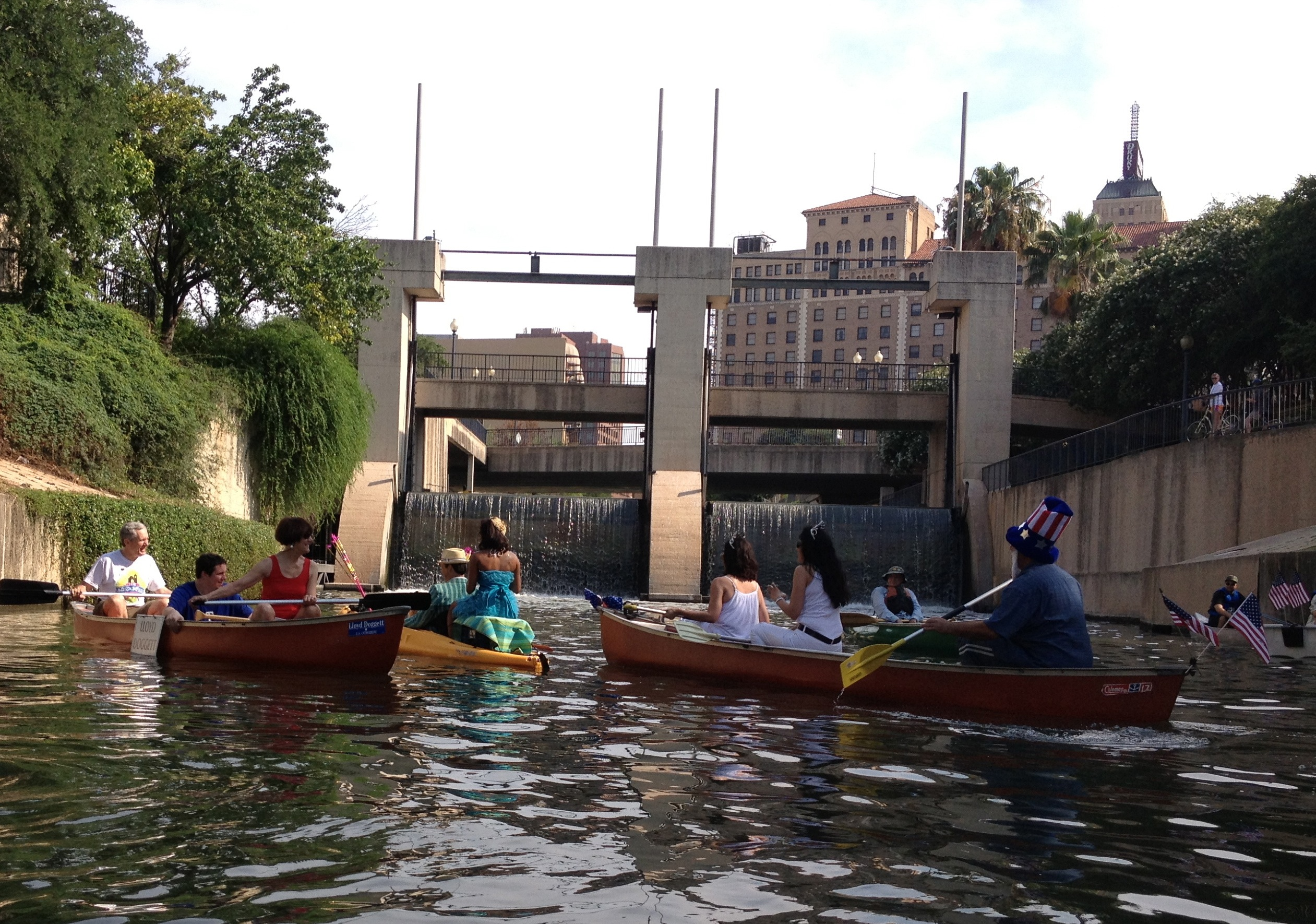 King William Regata paddlers floating in the San Antonio River at the Nueva Street Bridge & Dam. Photo by Robert Rivard.