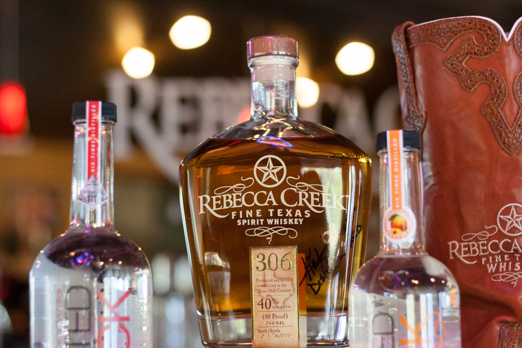 Rebecca Creek Texas Spirit Whiskey flanked by two different varieties of Enchanted Rock Vodka. Photo by Garrett Heath.