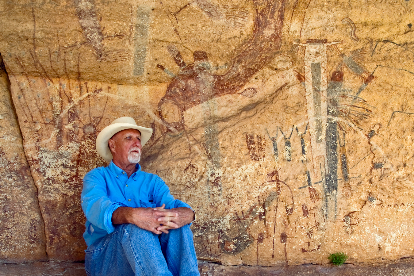 Harry Shafer is sits next to the White Shaman pictograph just off the banks of the Pecos River near Comstock, Texas. Photo by Al Rendon.