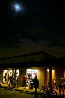 With the moon shining overhead, riders prep for the  Thursday night ride from Bike World on Broadway.
