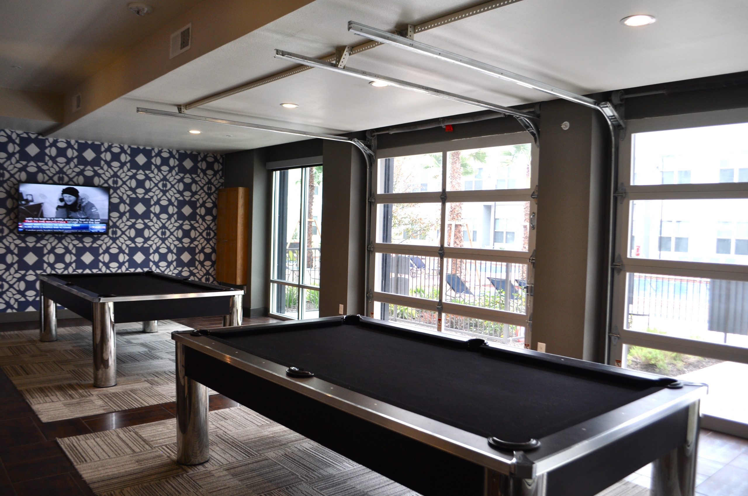 Pool tables at Tobin Lofts. The recreation area utilizes a former gas station/mechanic shop (hence the garage doors). Photo by Iris Dimmick.