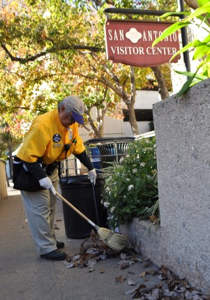 Helen Requenez, Maintenance Amigo supervisor sweeps a pathway near the San Antonio Visitor Center. Photo by Iris Dimmick.