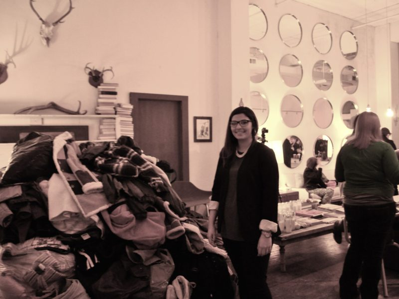 Cristina Flores and the huge pile of coats gathered during Cristina's First Anuual Coat Driveaganza at The Richter Co. Photo by Iris Dimmick.