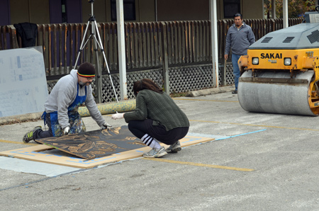 Kim Bishop, co-organizer of the Texas Size Print event with her husband Luis Valderas, and San Marcos-based artist Robin Orta prepare a pre-carved wooden block for the steamroller to create a relief print in the Centro Cultural Hispano de San Marcos parking lot. Photo by Jordan Gass-Poore'.