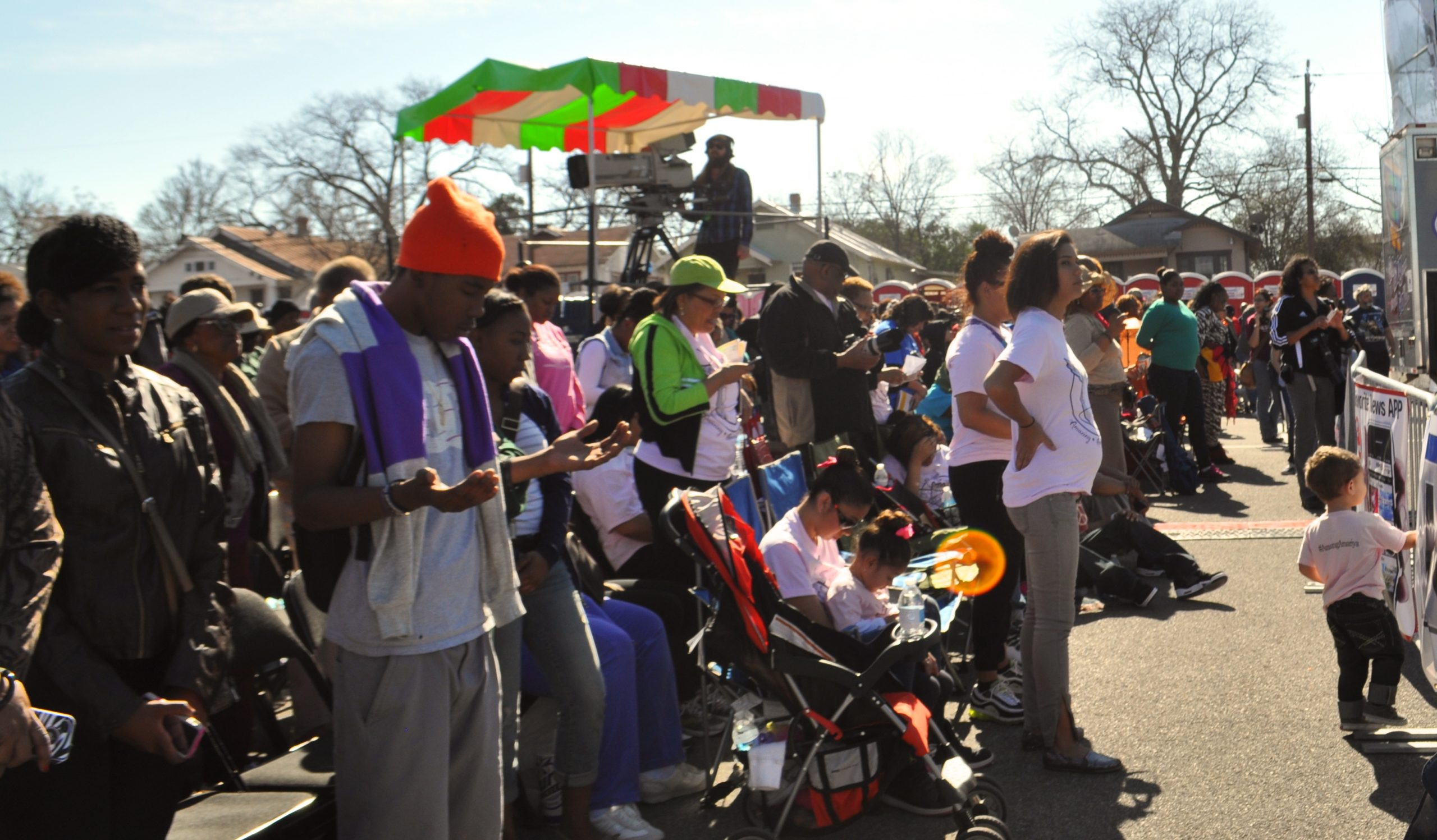 Attendees bow their heads and open their hands in prayer during the 2014 MLK Day ceremonies in Pittman-Sullivan Park. Photo by Iris Dimmick.