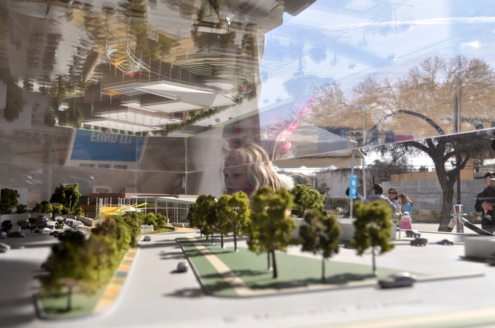 A young girl peers over Lake/Flato Architects' model of the future Do Seum (San Antonio Children's Museum). Photo by Iris Dimmick.