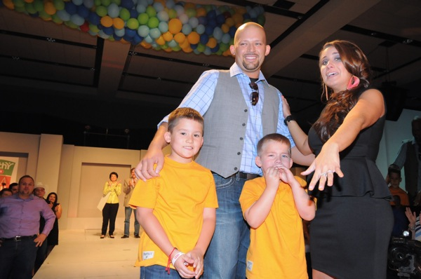 Ruben Cavazos stands with his blushing fiance, Melanie Cryer, and his two stage-shy sons just moments after he proposed marriage to her on stage at the 2013 H-E-B Slim Down Showdown award ceremony. Courtesy photo.