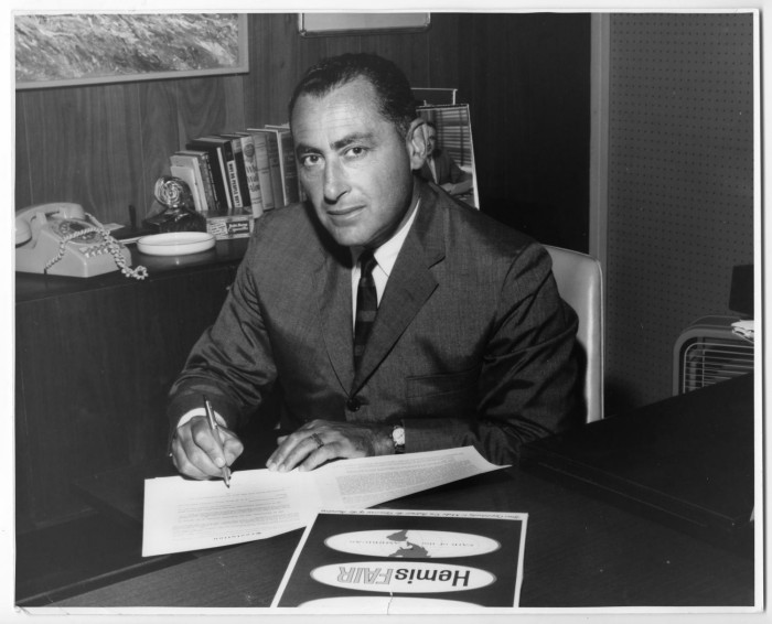 """William """"Bill"""" Sinkin signing a HemisFair document at his desk. Sinkin served as President of the Board of Directors of San Antonio Fair, Inc. from April 1963 to November 1964. Photo courtesy of The University of North Texas Libraries' Portal to Texas History."""