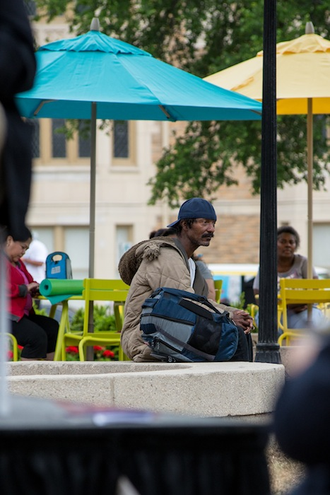 A seemingly down-and-out man watches the re-opening ceremony at Travis Park. Photo by David Rangel.