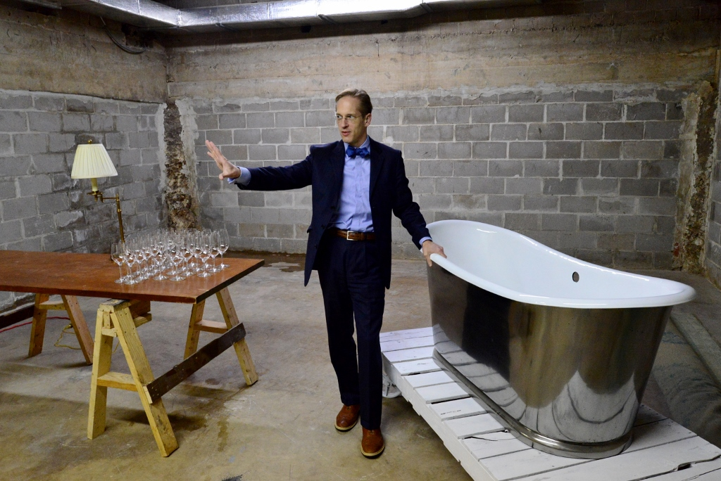 Leland Stone discusses a future bathtub display, which is placed upon an antique factory cart. Photo by Page Graham.