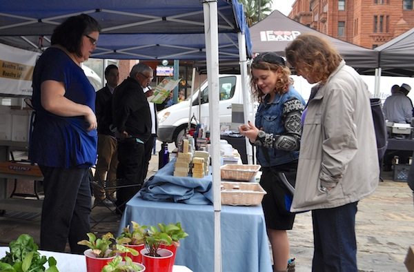 Nina Lieberman, founder of Soapmarked, looks on as a potential customer visits her booth during the Main Plaza Farmers Market. Photo by Iris Dimmick.