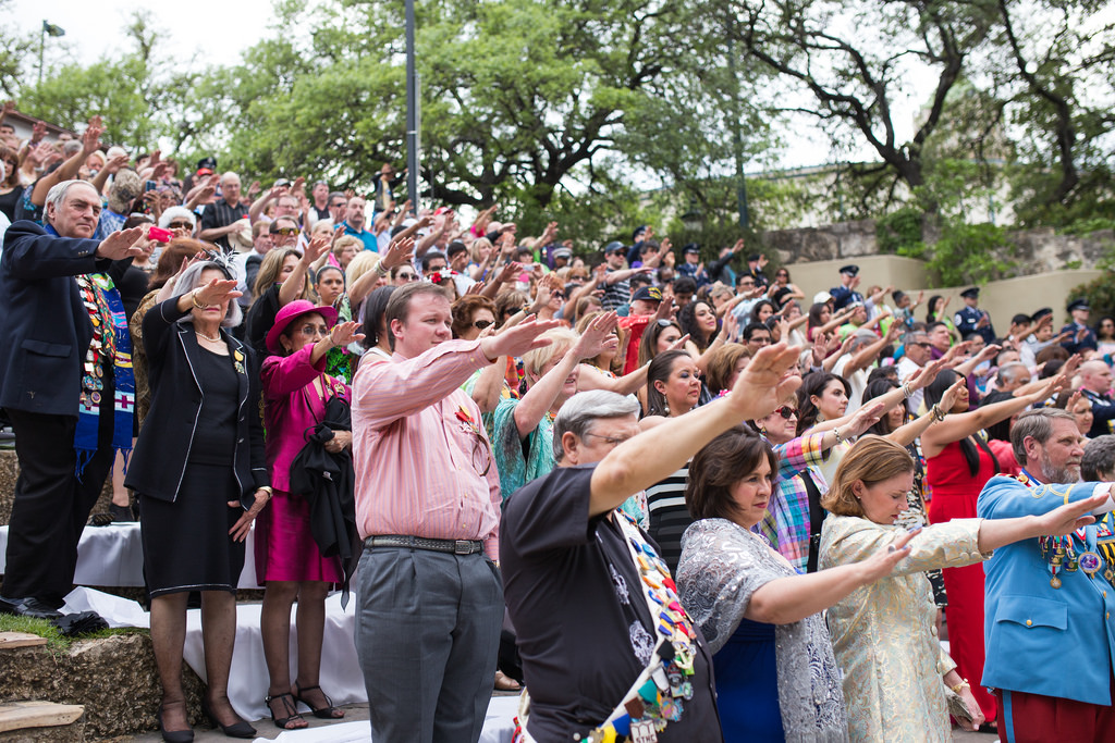 San Antonians reach out their hands in prayer during the crowning of El Rey Feo LXVI. Photo by Scott Ball.