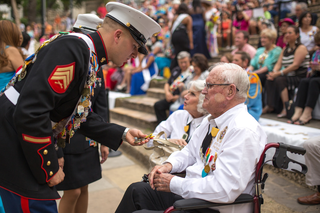 A Marine gives Jimmy Green's father (also a veteran) a medal during Green's crowning as El Rey Feo LXVI on Saturday April 19, 2014. Photo by Scott Ball.