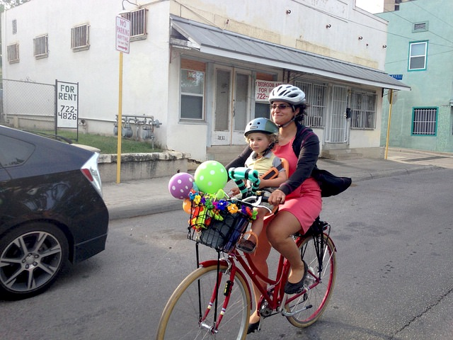 Anna CohenMiller Riding a bike to the Fiesta 2014 Texas Cavaliers River Parade. Photo by Doug CohenMiller.