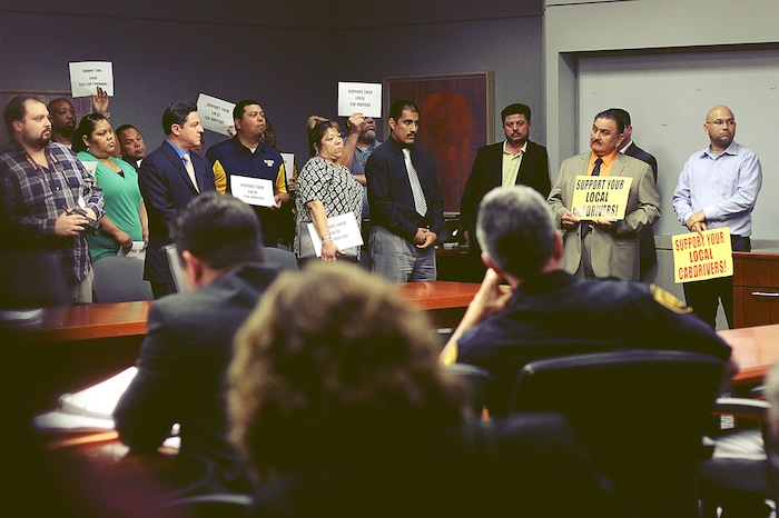 """Taxi drivers and media crowd the Public Safety Committee meeting room to hear talks about how authorities will deal with """"rideshare""""/transportation network companies. Photo by Brandy Rae Perez."""