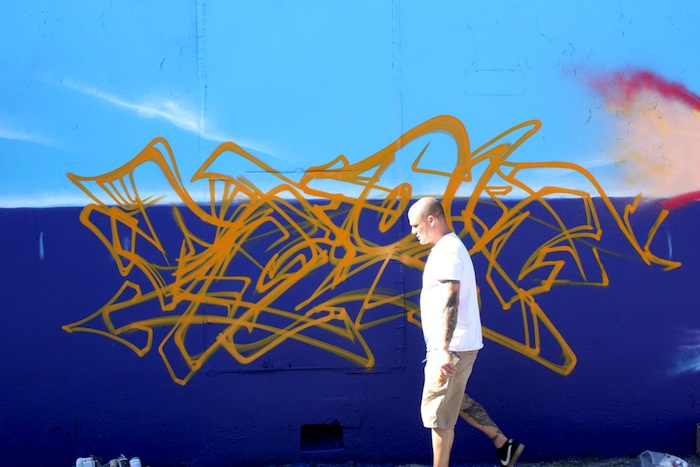 """Nathan Nordstrom, known as """"Sloke"""" in the graffiti world, works on a mural at The Paint Yard, a graffiti boutique located off San Pedro. Sloke, an Austin-based artist, draws inspiration from the progressive urban climate and the earth's natural state. He will be one of the artists featured this weekend during the Clogged Caps street art festival in San Antonio. Photo by Kay Richter."""