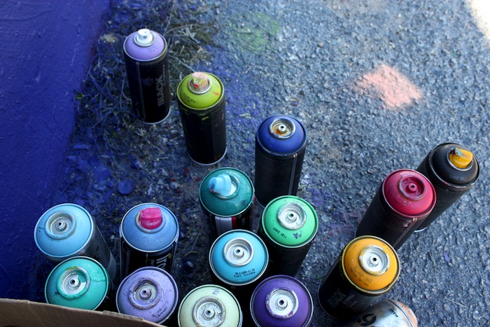 Paint cans pictured outside a live painting session at The Paint Yard. The majority of artists use specialized paints that can not be purchased at your local home improvement store but only from specialized vendors that sell within the area. Photo by Kay Richter.