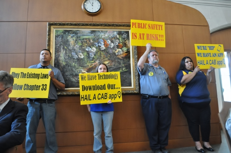 Citizens holds signs in protest against Lyft and Uber at the City Council Public Safety Committee meeting May 7, 2014. Photo by Iris Dimmick.