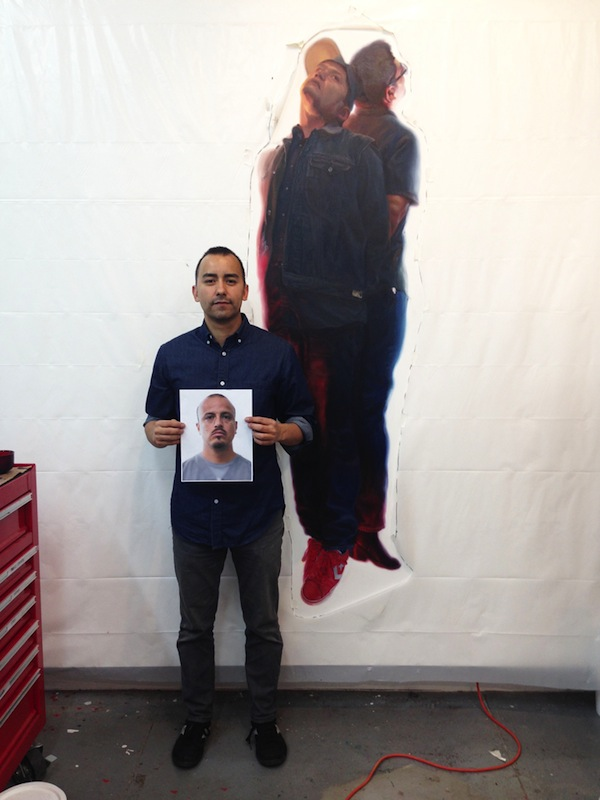 """Vincent Valdez holds one of 15 photographs of anonymous San Antonio men by local artist Mark Menjivar that will be on display alongside Valdez' series """"The Strangest Fruit."""" Photo by Taylor Browning."""