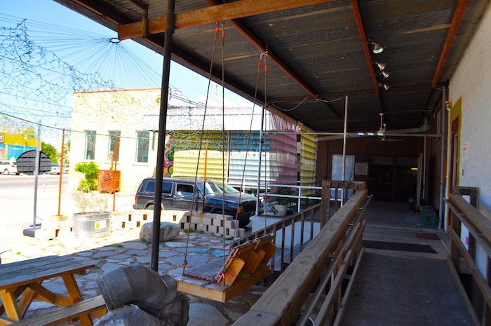 The patio space connecting studios and galleries on S. Flores at Lone Star Blvd. host the bulk of Second Saturday activity. During the evening, this patio will be packed with artists, patrons, and friends enjoying music, beer, and (of course) art. Photo by Iris Dimmick.