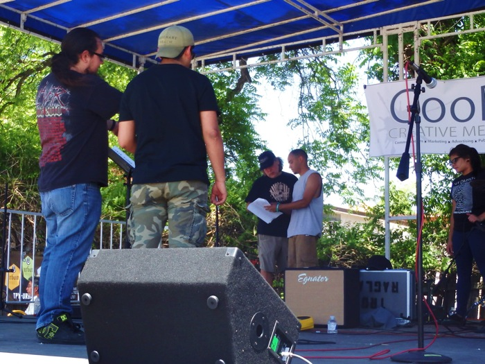 Pictured are students and Donnie Meals preparing the stage for the next band by miking drums and amplifiers.