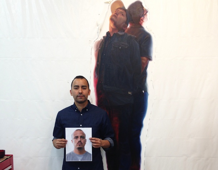 """Vincent Valdez holds a photograph of an anonymous San Antonio male used for a piece in his series """"The Strangest Fruit."""" Photo by Taylor Browning."""