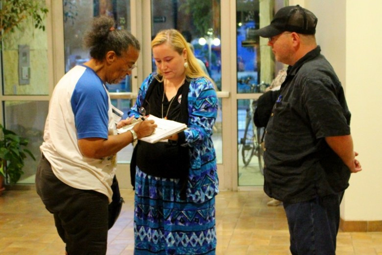 Streetcar foes gathered petition signatures before and after the meeting. Photo by Tami Kegley.