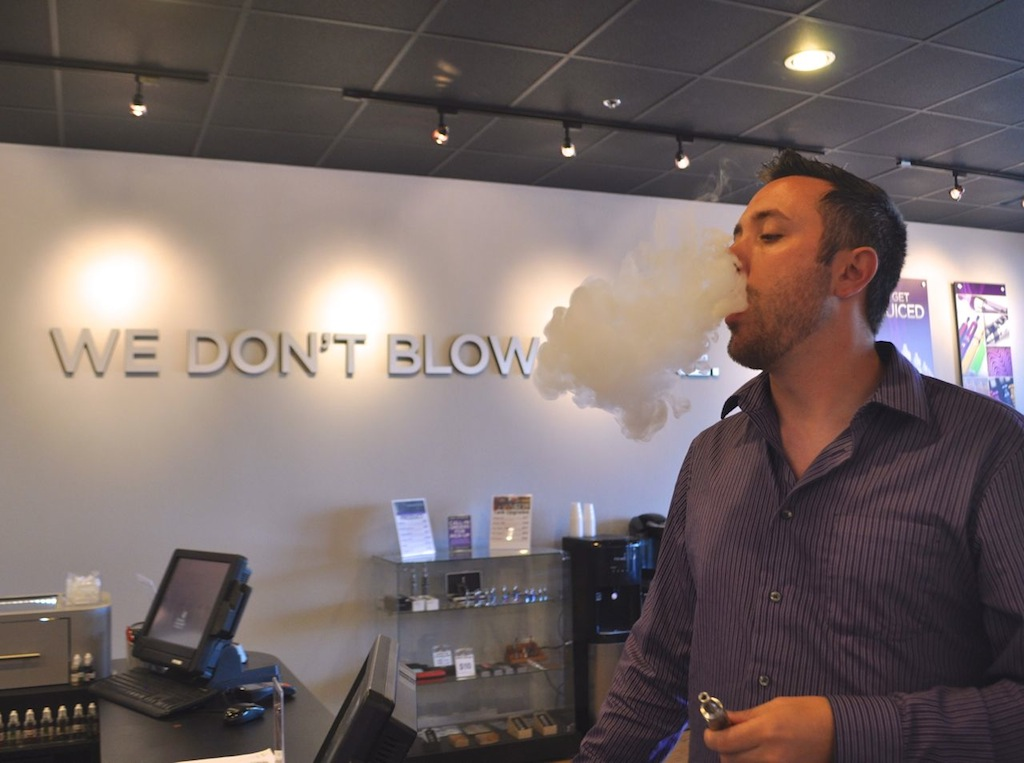 Monster Vape co-founder Christopher Zieg demonstrates that the plume of smoke from a vaporizer can be just as thick as tobacco cigarettes. Photo by Iris Dimmick.