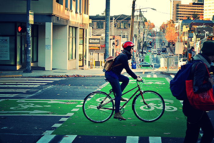 A cyclists utilizes the Capitol Hill separated bike lane. The newly-constructed streetcar line on Broadway Avenue can be seen in the distance. Photo courtesy of the Seattle Department of Transportation.