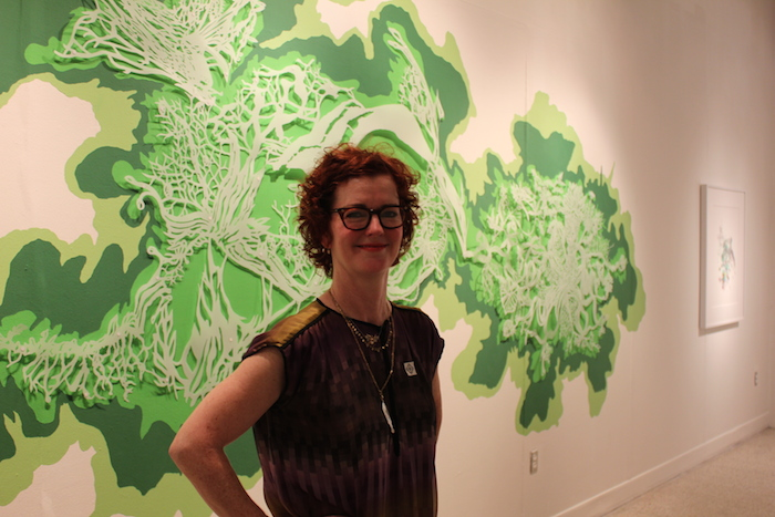 """Leigh Anne Lester stands with her piece at the Guadalupe Cultural Arts Center for the """"Flatland"""" exhibit. July 11, 2014. Photo by Melanie Robinson."""