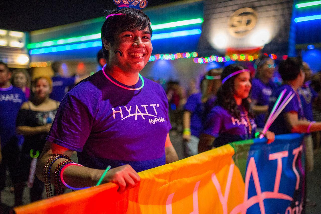"Robert Salas holds the Hyatt parade banner at the 2014 Pride ""Bigger Than Texas"" Parade. Photo by Scott Ball."