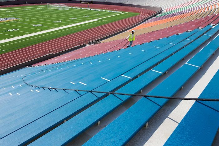A worker washes off the recently-installed, colorful benches at the Alamo Stadium. Photo by Scott Ball.