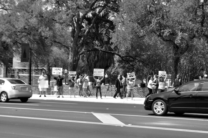 Protesters march and chant in front of UIW on Broadway Street in August 2014, calling for remembrance and justice for Cameron Redus. Photo by Iris Dimmick.