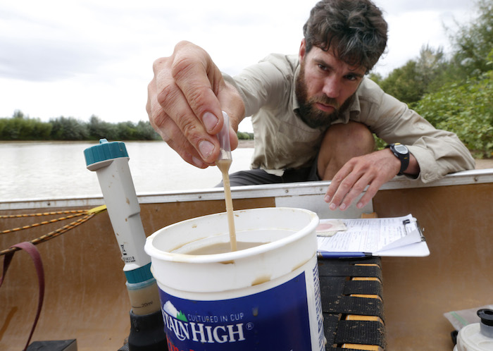 SOCORRO, NM - Colin McDonald takes a water sample before paddling down the Rio Grande River between Socorro and San Antonio, New Mexico. AUGUST 25 2014: CREDIT: Erich Schlegel/Disappearing Rio Grande Expedition